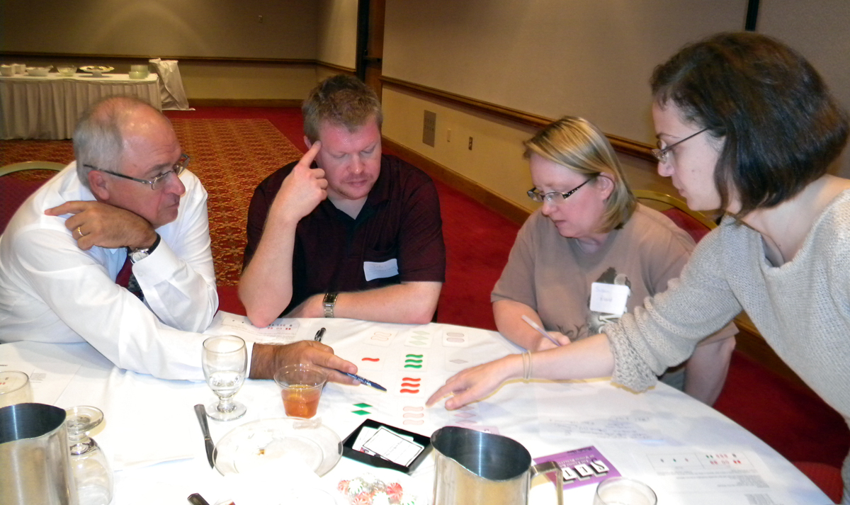 UNL's Chuck Friesen (left) and Courtney Gibbons (right) work with teachers John Sweeney and Susan Poland on the game of SET.