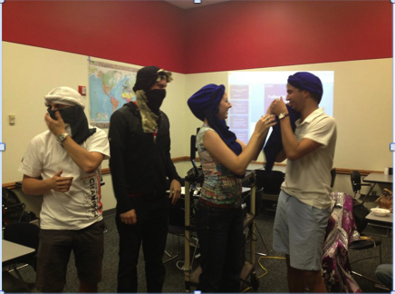 Gwyneth Talley teaches Grant Isaacson, (from left) Morgan Quijano and Adam Záhradník to wrap turbans during the UNL Globetrotters meeting on Oct. 23.  Talley acquired the skill while studying abroad in Morocco.