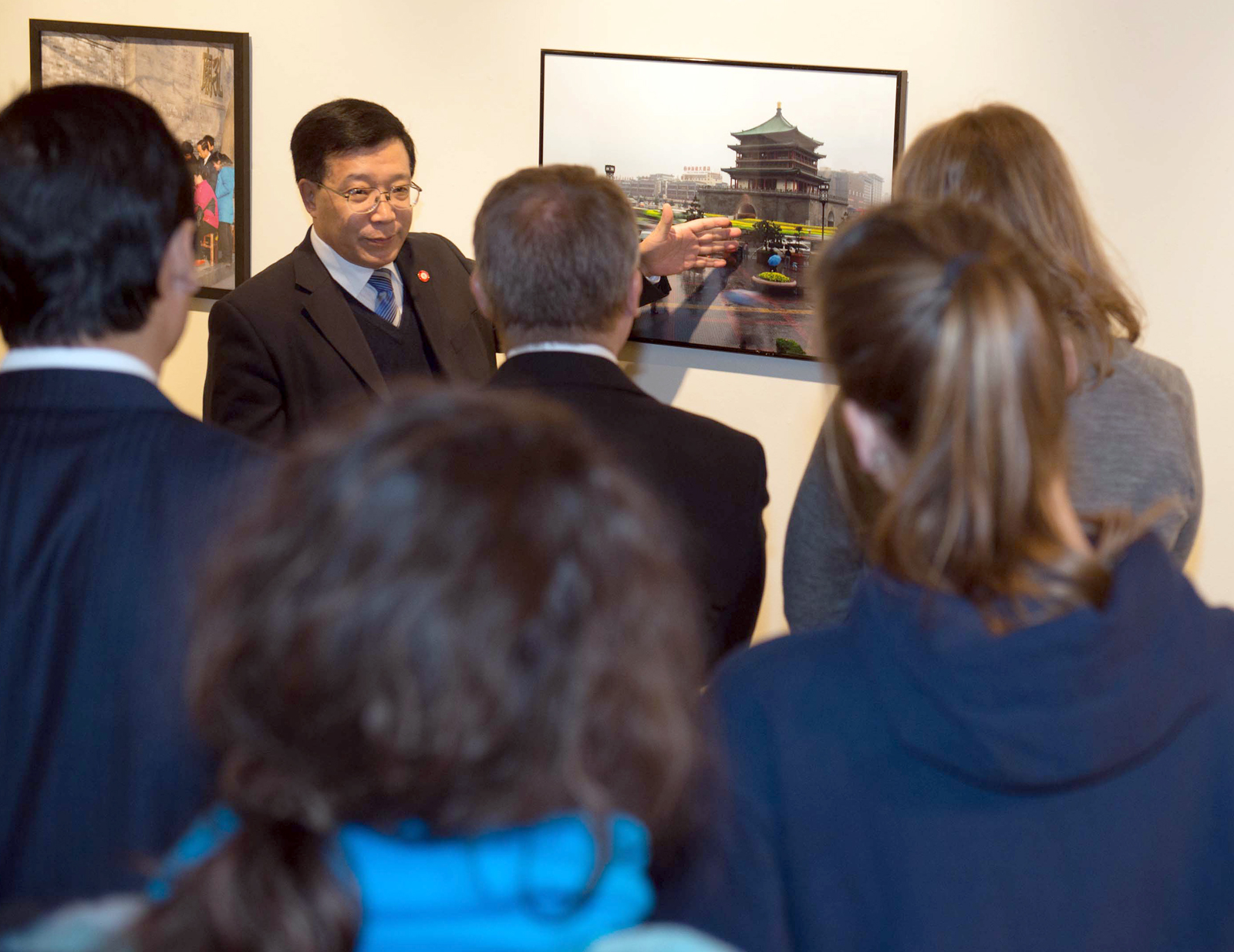 Song Xiaoping, vice president at Xi'an Jiaotong University, leads a Nov. 14 tour of a photography exhibition in Richards Hall.