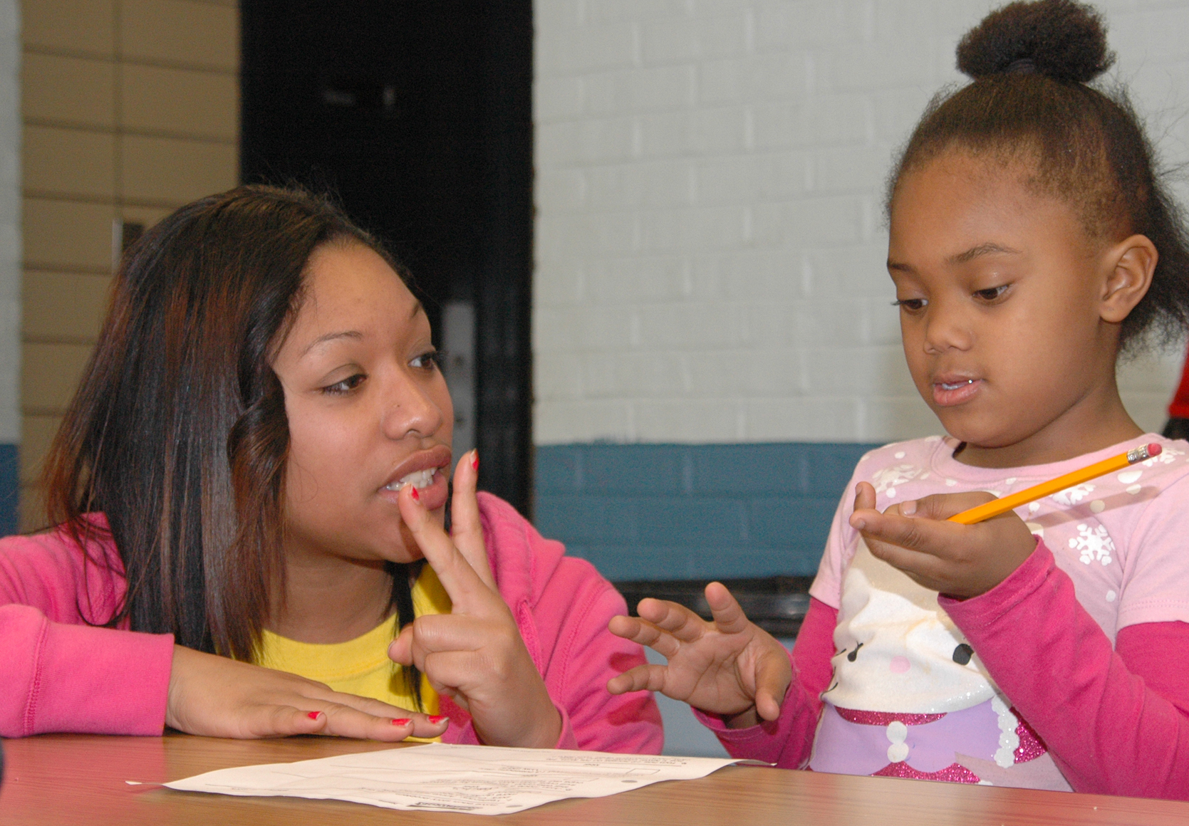 A UNL student helps a child with homework during a Martin Luther King Jr. Day outreach project in 2011. Three UNL researchers are identifying the economic value of Nebraska's investments into early childhood development programs.