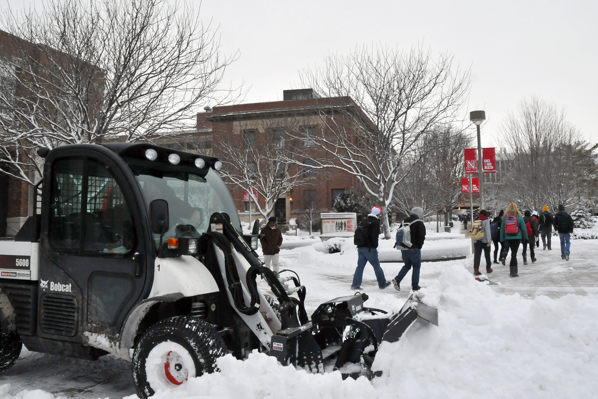 Tanner Hilzer waits to plow more snow as students pass the north side of the Nebraska Union on Jan. 30. Landscape Services employees started clearning snow from campus at 2 a.m. Wednesday.