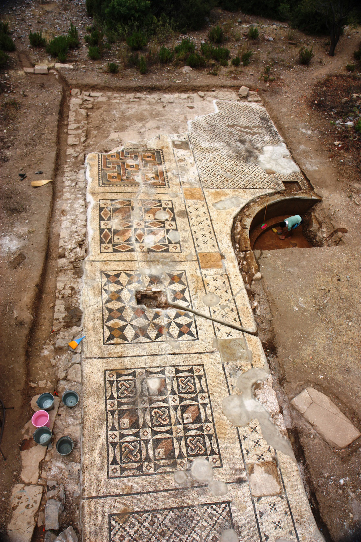 An overhead perspective of the roughly 40 percent of the Roman mosaic uncovered so far. The mosaic measures approximate 25 meters by seven meters and served as the forecourt for the adjacent large bath. Researchers expect its total area to be about 1,600