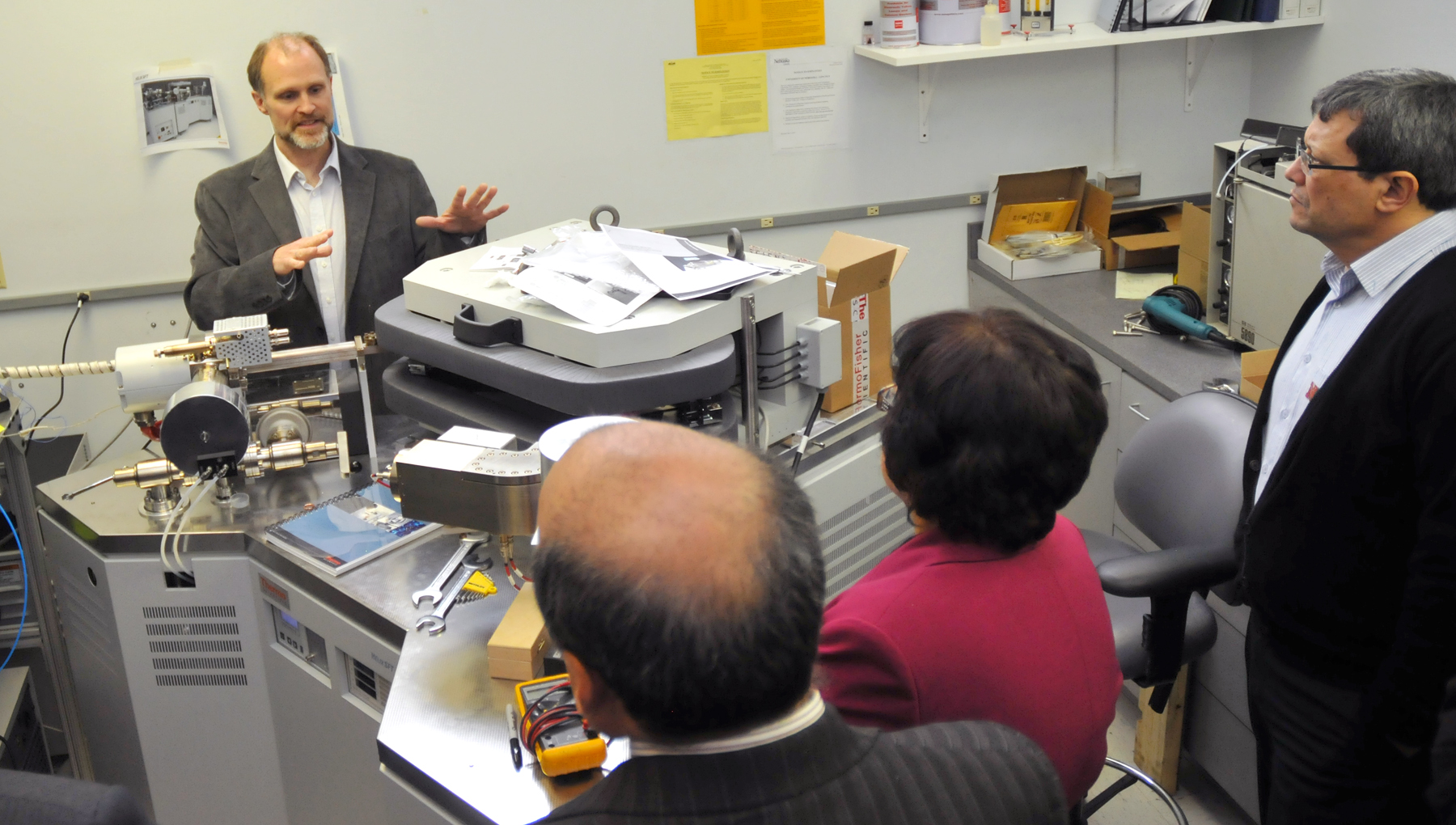 Dan Snow, director of services at UNL's Water Sciences Laboratory, discusses a nitrogen gas mass spectromenter with members of the Founders Committee on March 21.