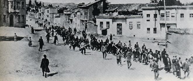 Armenian civilians, escorted by armed Ottoman soldiers, are marched through Harput to a prison in the nearby Mezireh, April 1915.