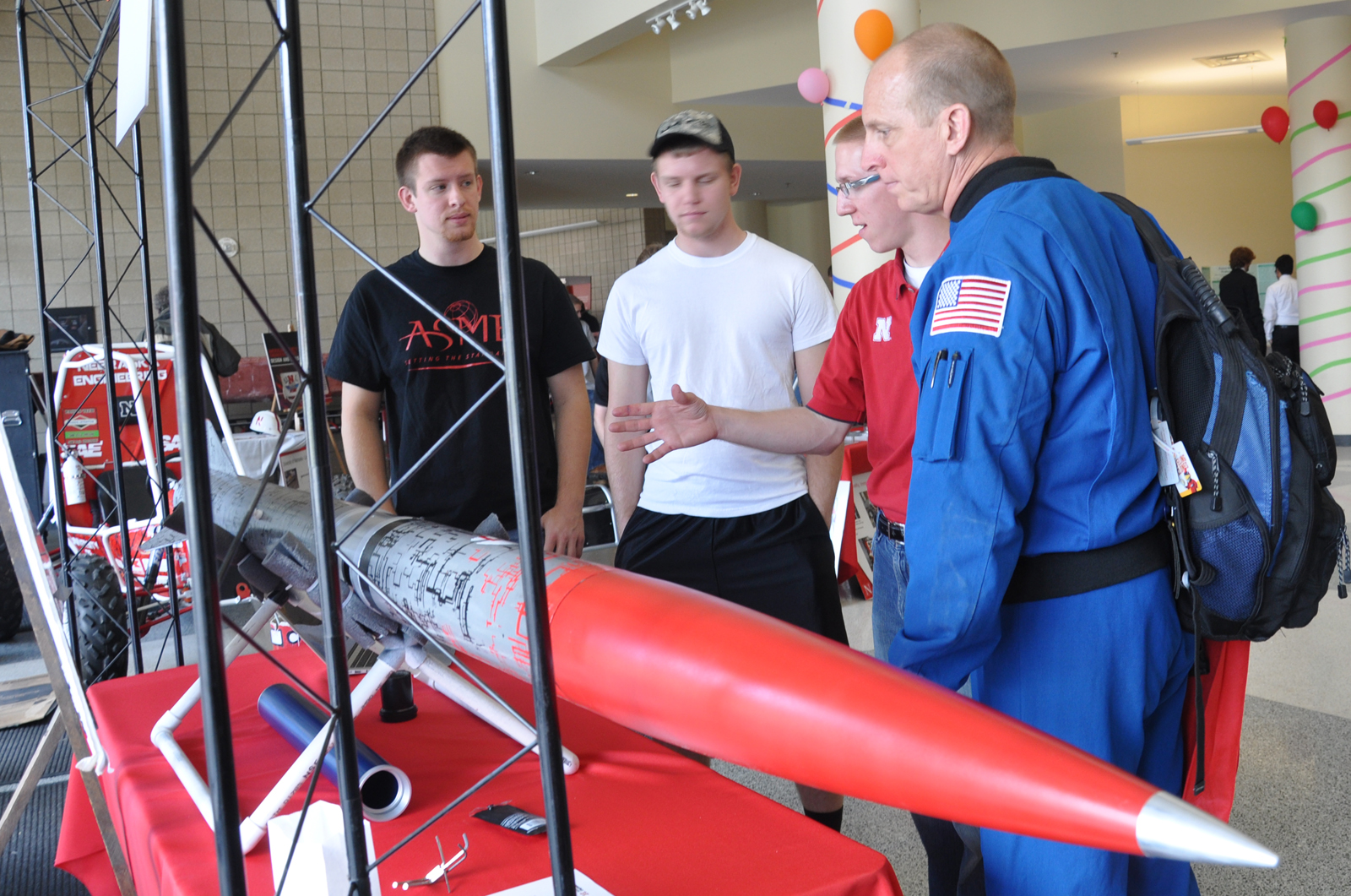 (From left) Mechanical engineering students Alex Drozda and Brad Christensen listen as civil engineering student Bryan Kubitschek, talks about a rocket with former NASA astronaut Clay Anderson on April 12 at Engineering Week Open House.