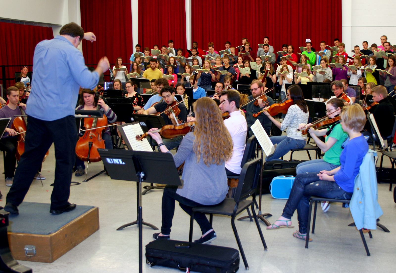 "Tyler White conducts the orchestra and combined choruses during a ""Requiem"" practice."