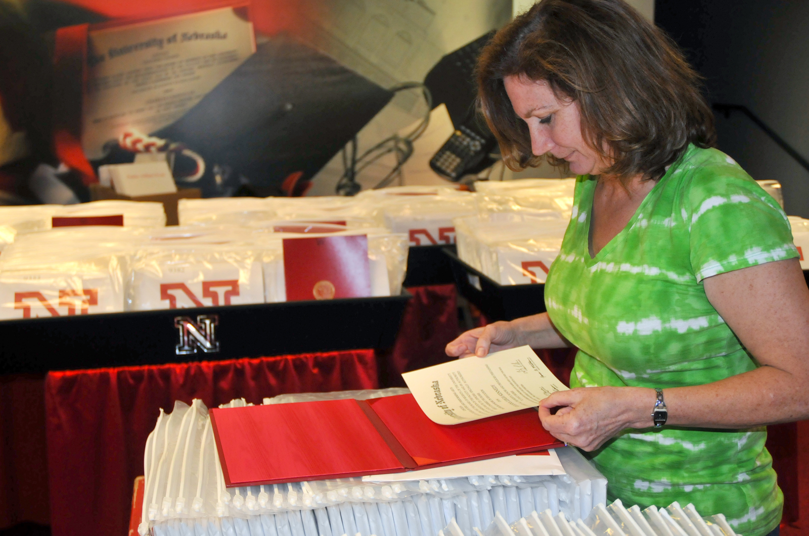 Patti Jones, a senior office associate in the Registrar office, puts together a diploma that will be handed out during UNL's May 4 commencement exercises in Memorial Stadium.