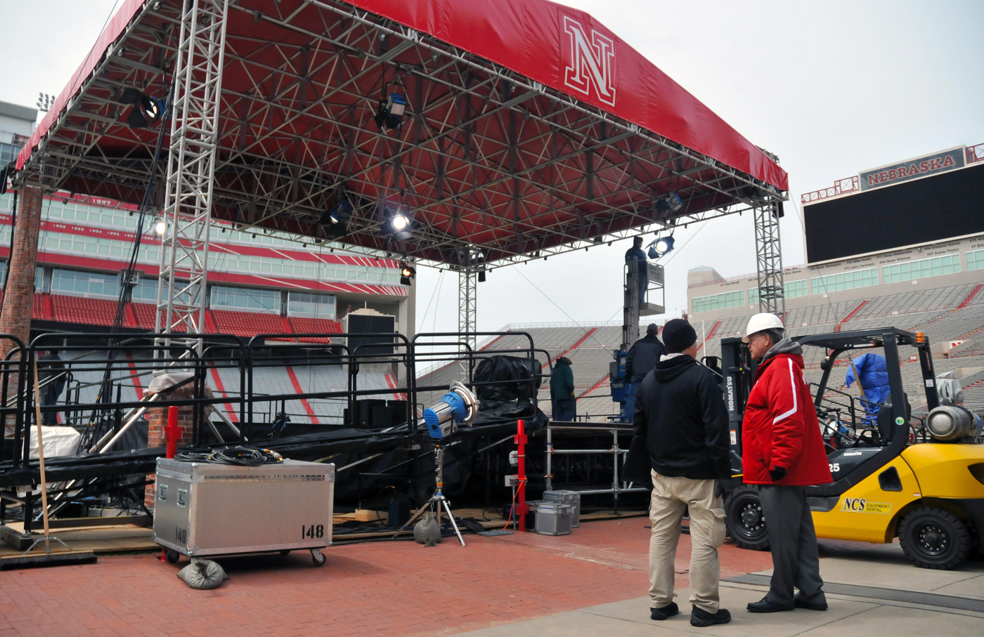 UNL's Butch Hug (right) talks with Tom Curtright, president of Comprehensive Design Solutions, as lighting is adjusted on the commencement stage in Memorial Stadium.
