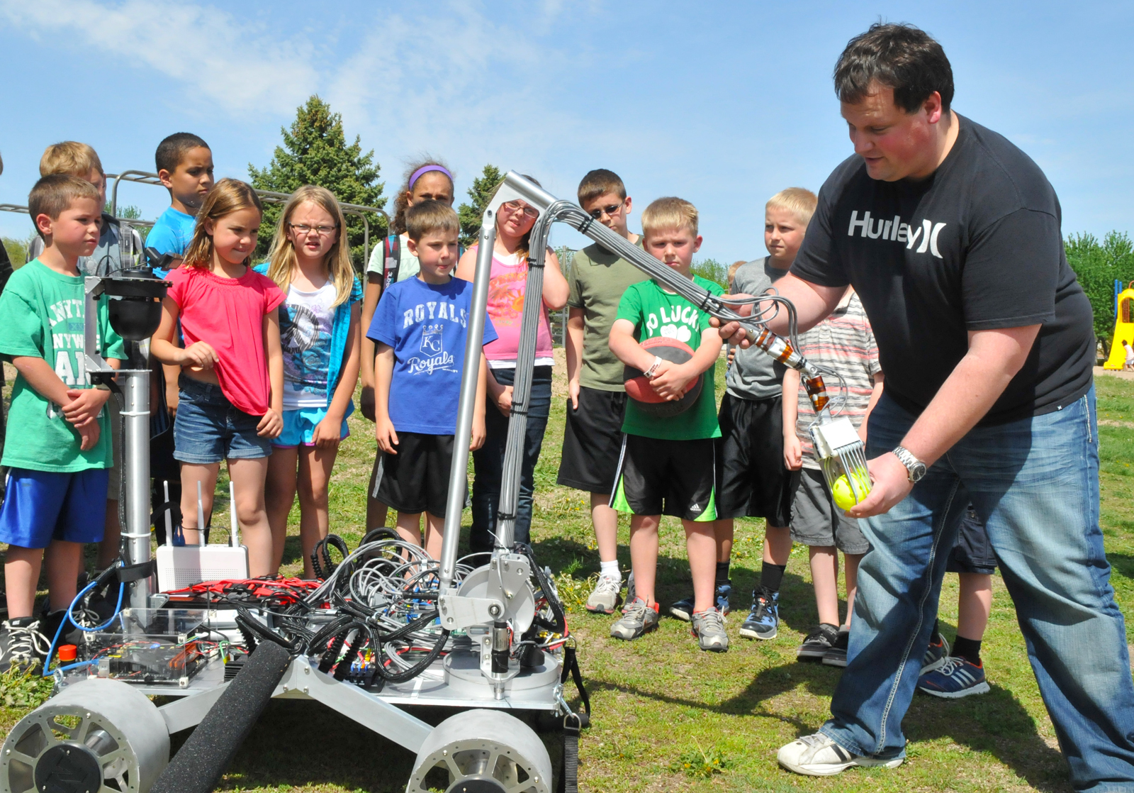 Joe Bartels (right) shows Zeman Elementary students how a robot developed by UNL engineering students will be used to pick up rocks. The robot was developed for a NASA-led robotics competition.