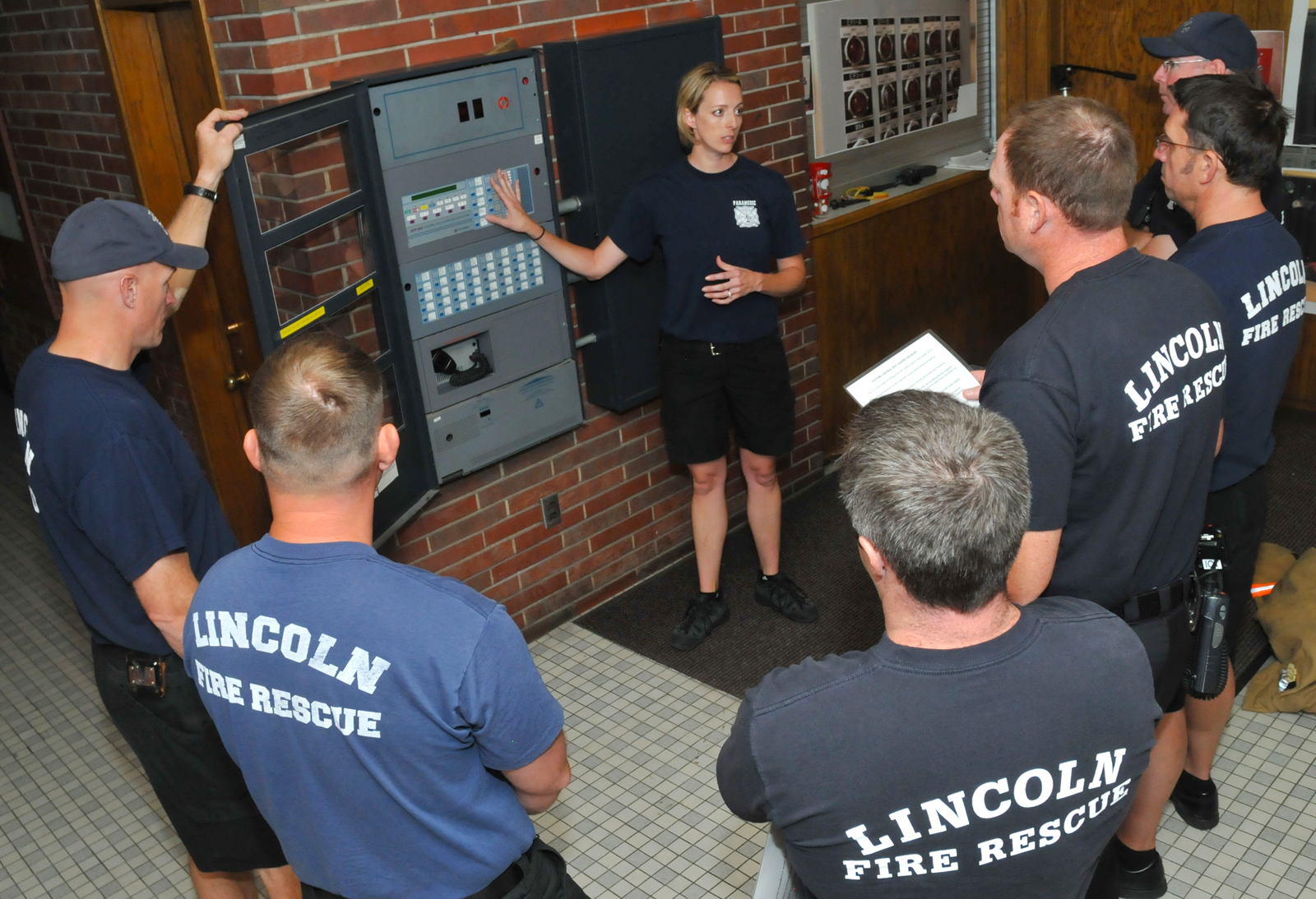 Jamie Pospisil (center) discusses the Pound Hall fire panel with fellow members of Lincoln Fire and Rescue on June 11. First responders have been using Pound Hall to train for high-rise fires. (Troy Fedderson, University Communications)