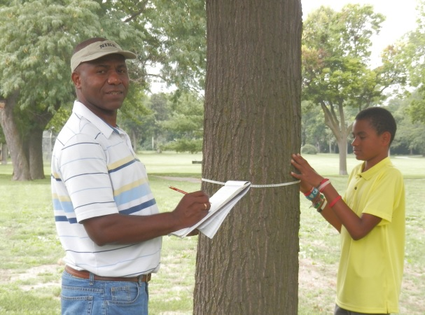 William Ballesteros collects data with the help of a young volunteer. The most accurate way to estimate stored carbon and subsequently carbon dioxide equivalent is to directly measure the trees on a specific place.