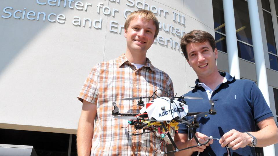 Carrick Detweiler (left) and Sebastian Elbaum hold a prototype of the water sample-collecting drone they are building. (Troy Fedderson | University Communications)