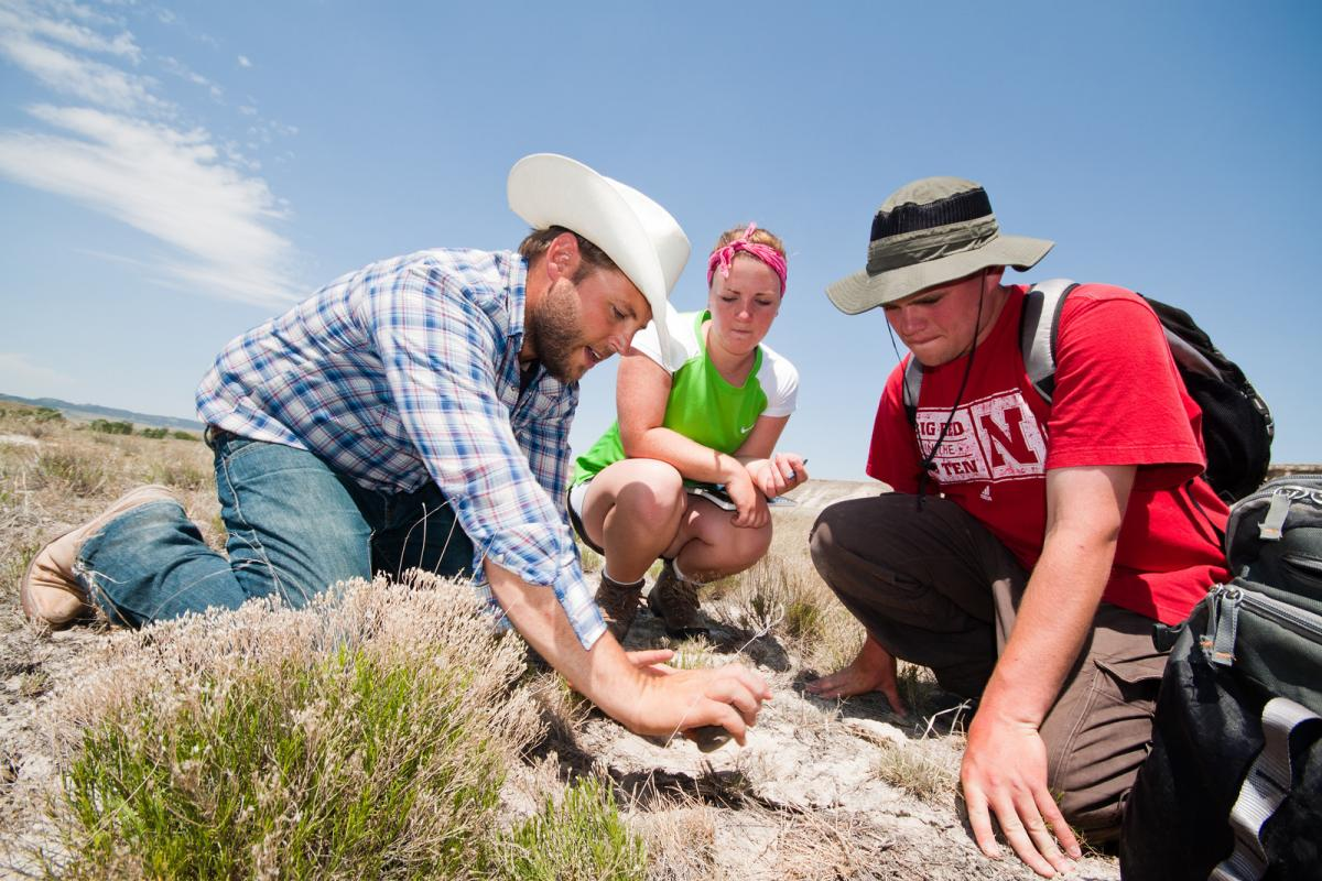 Matt Douglass (left) conducts research in the field with students.