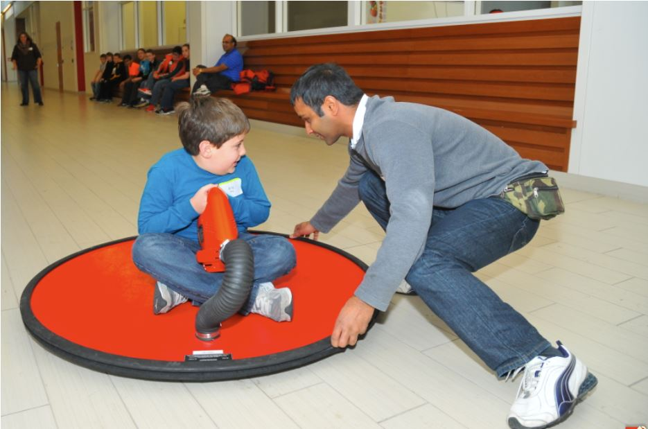 A fifth grader rides a hover craft during a Saturday Science.  Photo Credit: Troy Fedderson