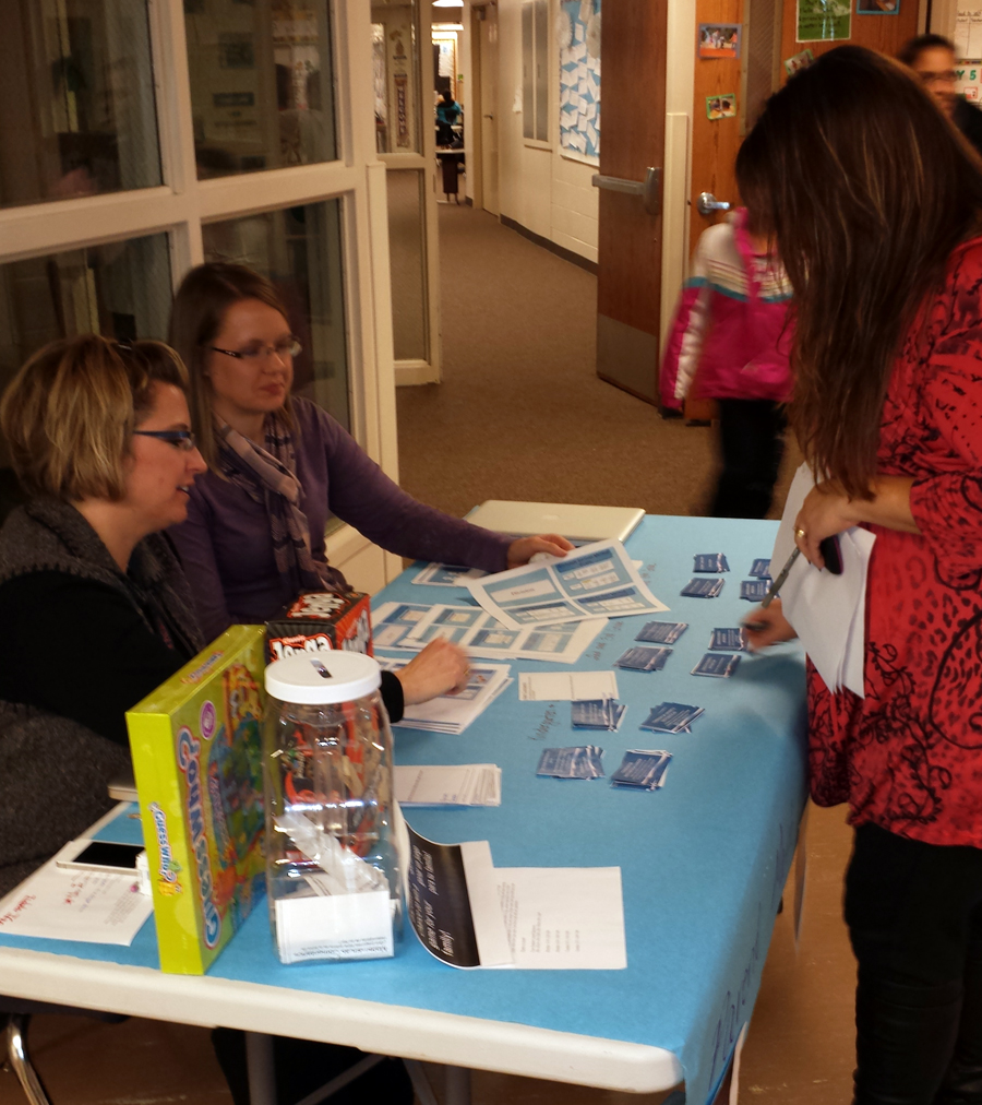 Angie Roby and Katie Keasling talk to a parent about math.