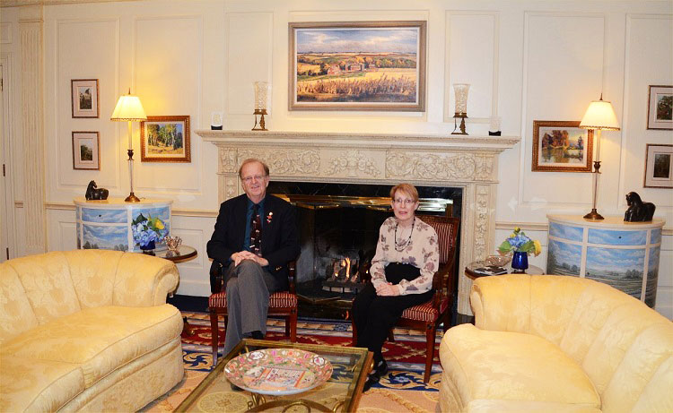 Ken Dewey and his wife Oma sit near the fireplace in the living room of the Governor's Residence.