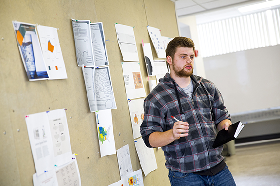 Andrue Oglesby receives suggestions on his research direction during a class review on March 4. Photo by Craig Chandler, University Communications.