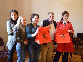 Miles Bryant (second from right) presents UNL tote bags to a group of Georgian students.