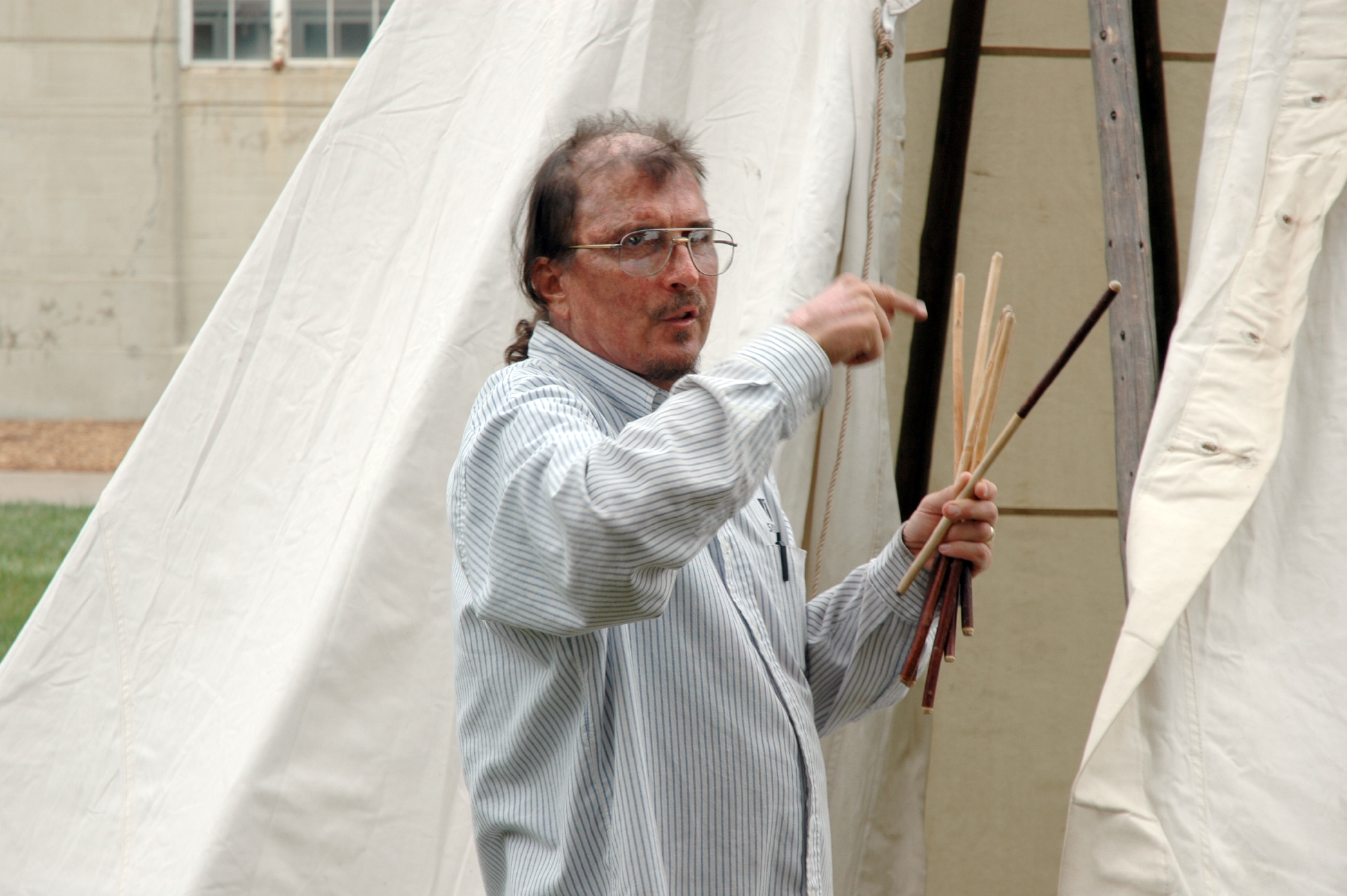 Mark Awakuni-Swetland describing the use of the chokecherry lacing pins for buttoning up the front of the tipi to his Omaha language class on the lawn east of Memorial Stadium in 2004.