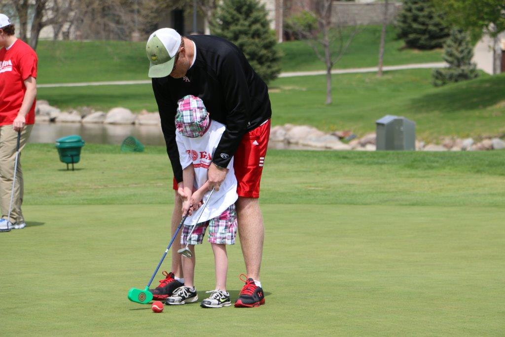 A PGM student helps a Special Olympian with golf swing.