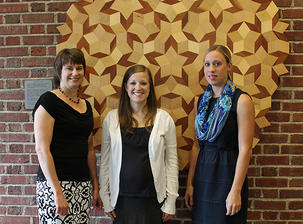 From left: Kelli Roeber-Schoening, Tiffany Powers and Shannon Wiig, who all earned their MAT degrees on August 16, 2014, worked on a mathematics problem involving the Penrose tilings as shown in this display in Avery Hall.