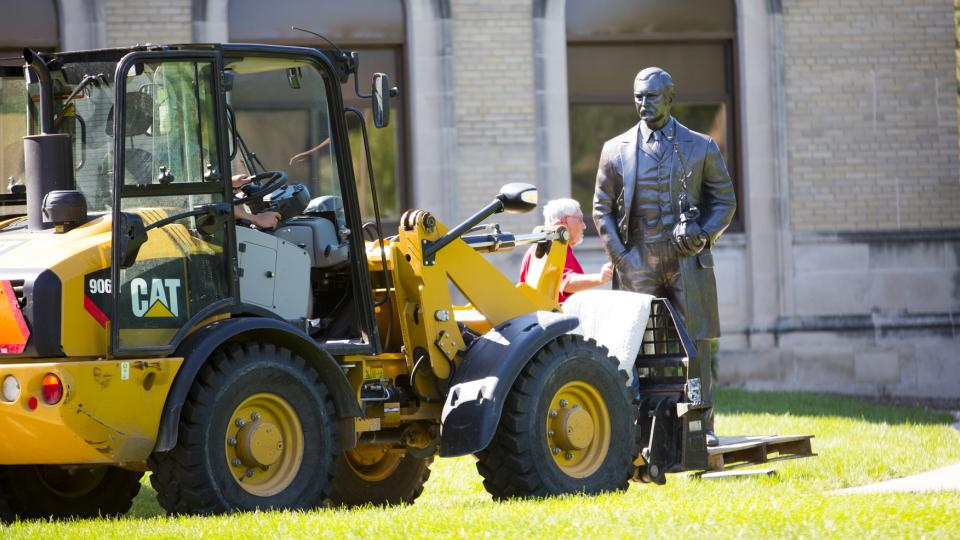 Workers use a tractor to position the new life-sized sculpture of J. Sterling Morton on East Campus on Sept. 8. The sculpture is one of four honoring Nebraskans who have served as U.S. Secretary of Agriculture. (Craig Chandler | University Communications)