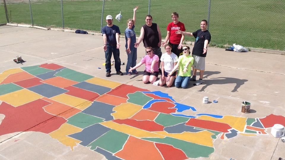 UNL students who are part of the Geography Student Organization pose by the nearly complete U.S. map painted on a Scribner-Snyder Community Schools playground.