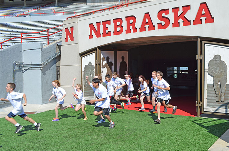 UNL Weather Campers rush the field at Memorial Stadium on June 11. Campers conducted a microclimate study of the facility. (Mekita Rivas | Natural Resources)