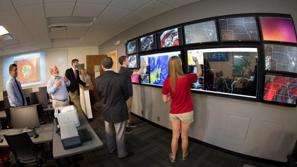 Clinton Rowe, left, professor of Earth & atmospheric sciences, describes the touch screen video wall. (Craig Chandler | University Communications)