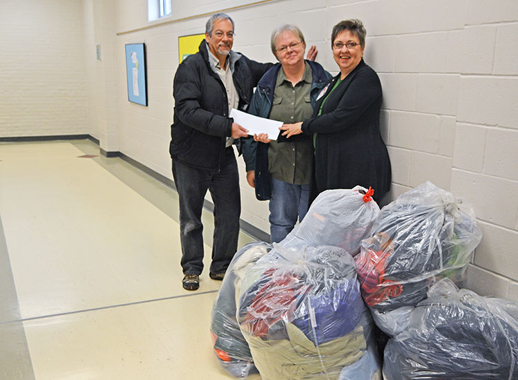Dennis Ferraro and Dee Ebbeka (center), members of SNR's community engagement committee, present Clare Nelson with donations on Dec. 9. (Mekita Rivas | Natural Resources)