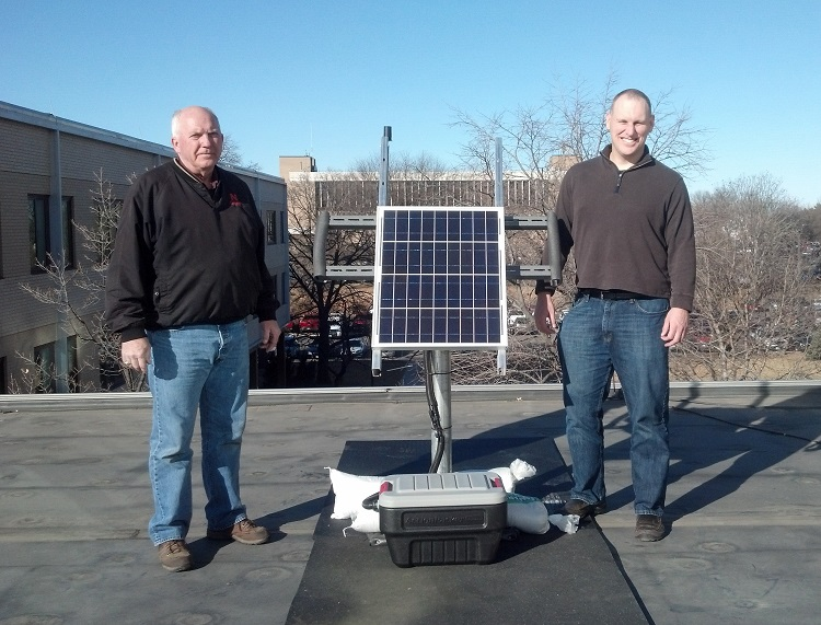 Rick Perk (left), assistant geoscientist, and Brian Wardlow, CALMIT director and associate professor, with the PhenoCam on Hardin Hall's roof. (Photo courtesy Bryan Leavitt)