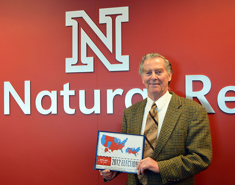 """Clark Archer holds his new book, """"Atlas of the 2012 Elections."""" (Mekita Rivas 