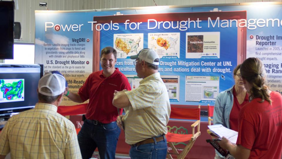 Brian Fuchs (second from left), a National Drought Mitigation Center climatologist and U.S. Drought Monitor author, discusses the prospects for rain with visitors to Husker Harvest Days, an agriculture trade show held each September in Grand Island.