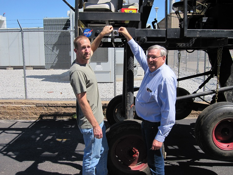Joe Lehnert (left) and Roger Hoy affix a Nebraska Tractor Test Lab decal to Goliath to commemorate the completion of the effort and the move of the machine back to the Agricultural Research and Development Center near Mead, Nebraska. (Courtesy photo)