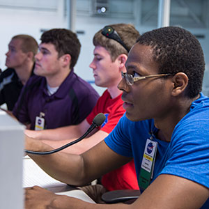 Sitting in NASA's Test Com room at Johnson Space Center in Houston, Texas, UNL Air and Space Research team members instruct divers on how to use a tool they had designed for possible use in space.