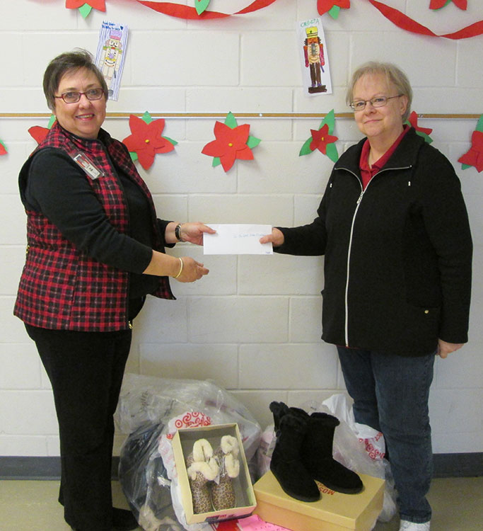 """Dee Ebbeka (right) presents Clare Nelson with the donations from the 2015 """"Coats for Clinton"""" drive."""
