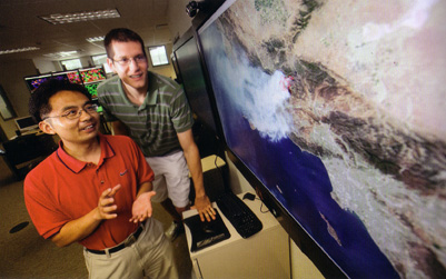 UNL professor Jun Wang and grad student David Peterson examine the map of a wildfire.
