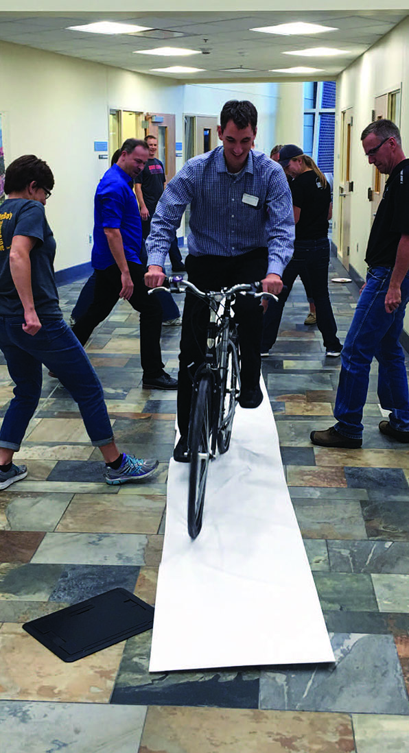 """Tom Clark takes the wheels in a session on """"Bicycle Tracks"""" led by James Tanton at a recent meeting of the Northwest Iowa Math Teachers' Circle."""