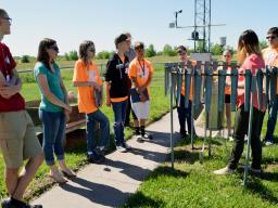 Barb Mayes Boustead, National Weather Service meteorologist and University of Nebraska-Lincoln graduate, gives Weather Camp students information on the rain gauge and its data Tuesday, June 7, 2016, at the station in Valley, Nebraska.