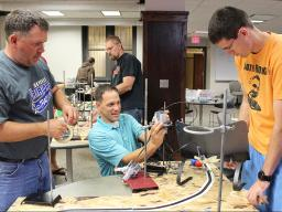 Jesse Andres (center), instructor for CSCE 890: Robotics for Teachers, helps Dan Schaben (left) and Matt James set up their robots.