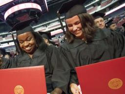 (From left) Julia Storm, Davetta Nelson and Gianna Astorino look over their diplomas in criminal justice during the all-university commencement ceremony Aug. 13 at Pinnacle Bank Arena.