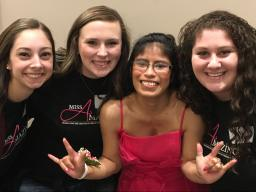 UNL seniors Stefanie Gentile, Hayley Brooks and Aly Lerman pose with Carmita Wilson after being paired with her at the 2016 Iowa Miss Amazing Pageant.