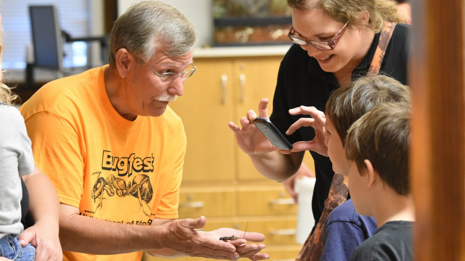 Tom Weissling | Department of Entomology. Entomology Professor Fred Baxendale introduces Vinnie the vinegaroon to a BugFest guest in 2015.