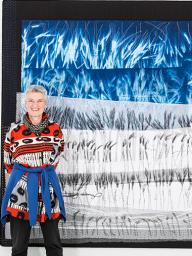 "Pauline Burbidge, pictured in front of ""Wheat & Barley Fields,"" will speak at the International Quilt Study Center & Museum on Oct. 14. (Photo by Phil Dickson)"