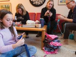 """Nylah Mossop (left) uses her fingers to knit a scarf during the launch of the """"Scarves for Kids"""" project on Nov. 20. The event was organized by Jo Ann Emerson (right) and Sandra Williams (not pictured). Other participants included (left of Emerson) Amanda"""