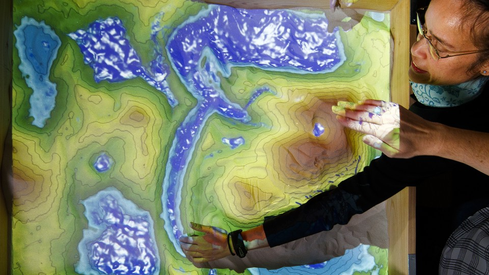 Leilani Arthurs, assistant professor of Earth and atmospheric sciences, sculpts a river bed into the new augmented-reality sandbox in Bessey Hall. Craig Chandler | University Communication