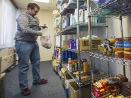 Cody McCain, a sophomore accounting and agribusiness major from Aurora, places donations on shelves in the university's current food pantry. McCain is the coordinator for the food pantry, which is located in the Lutheran Center. The university is opening