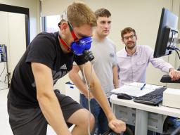 Assistant professor Karsten Koehler (far right) works with students in his exercise science lab in the Department of Nutrition and Health Sciences.