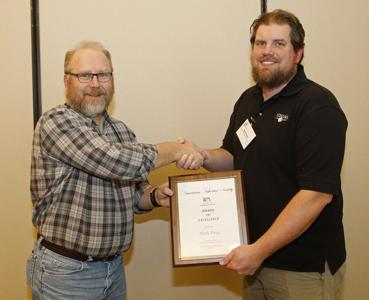 Mark Pegg, left, fisheries ecologist with the School of Natural Resources, accepts the Nebraska Chapter of the American Fisheries Society Award of Excellence.