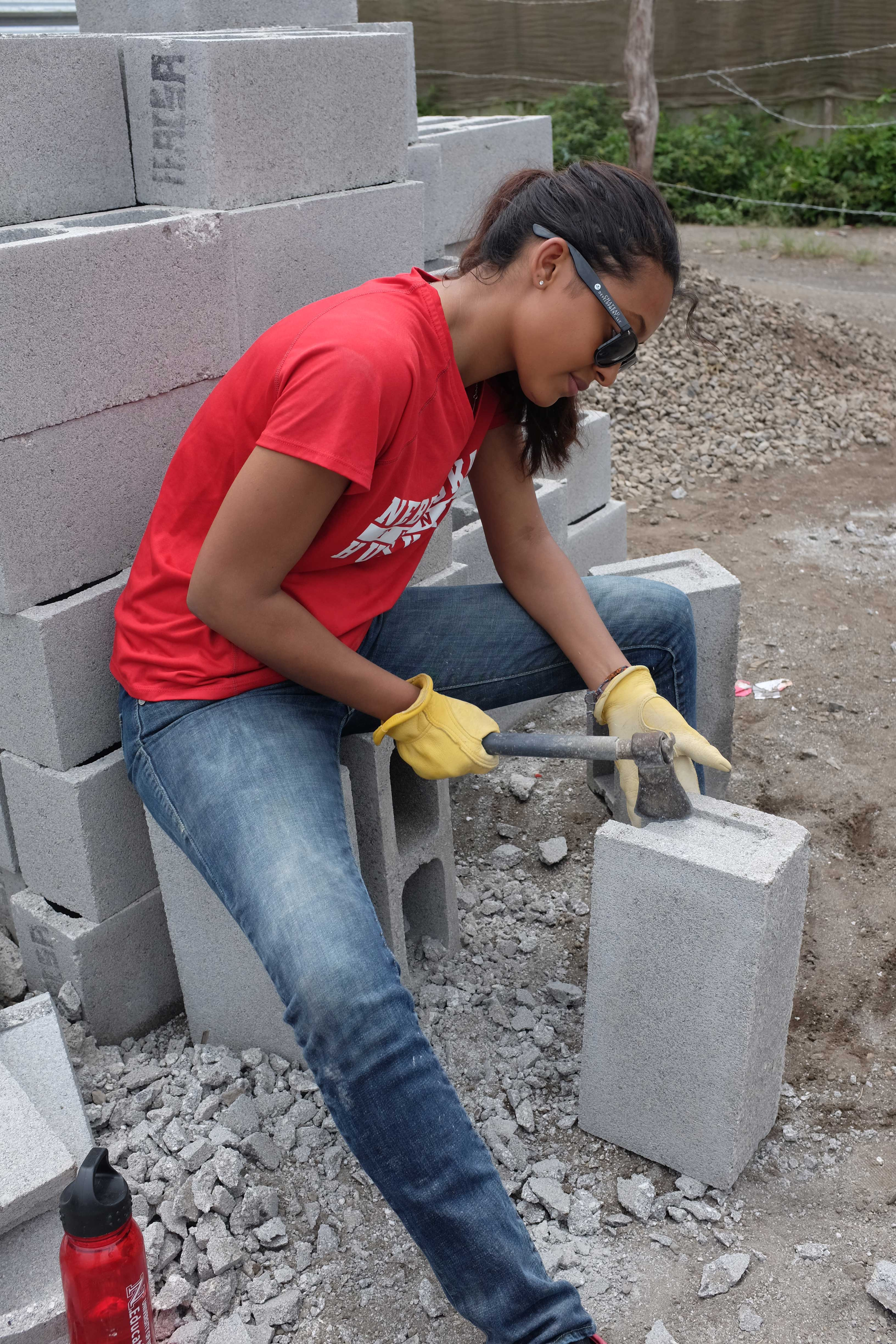 Student chops bricks to build hurricane resistant homes in Guatemala.